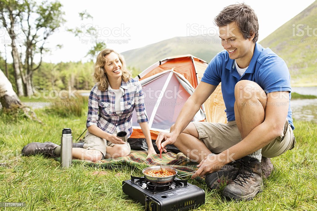 Man Prepares Meal On a Camping Stove stock photo