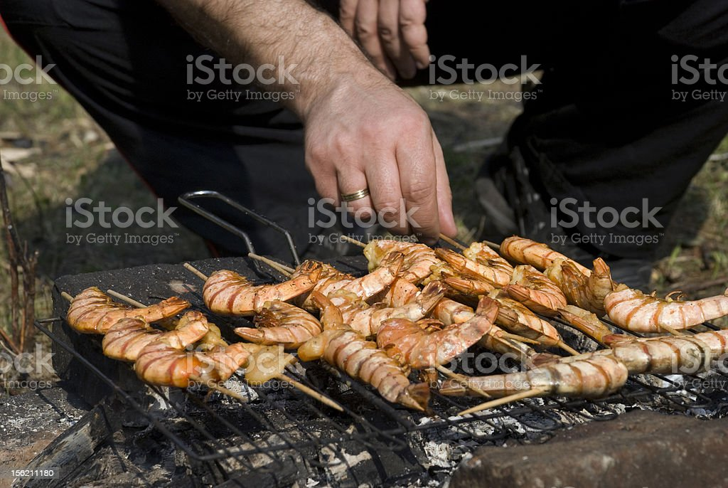 Man prepares shrimps on a grill royalty-free stock photo