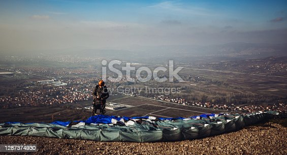 Man prepares to fly with paraglider