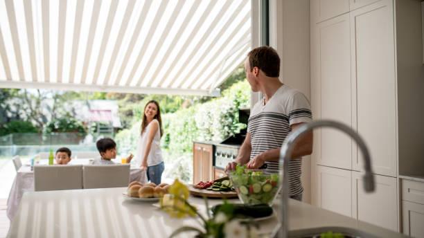 mann bereitet gemüse in der küche - outdoor esszimmer stock-fotos und bilder