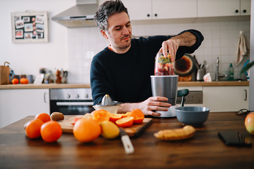 Man preparing a healthy breakfast at home, cutting fruits for a smoothie in his kitchen.