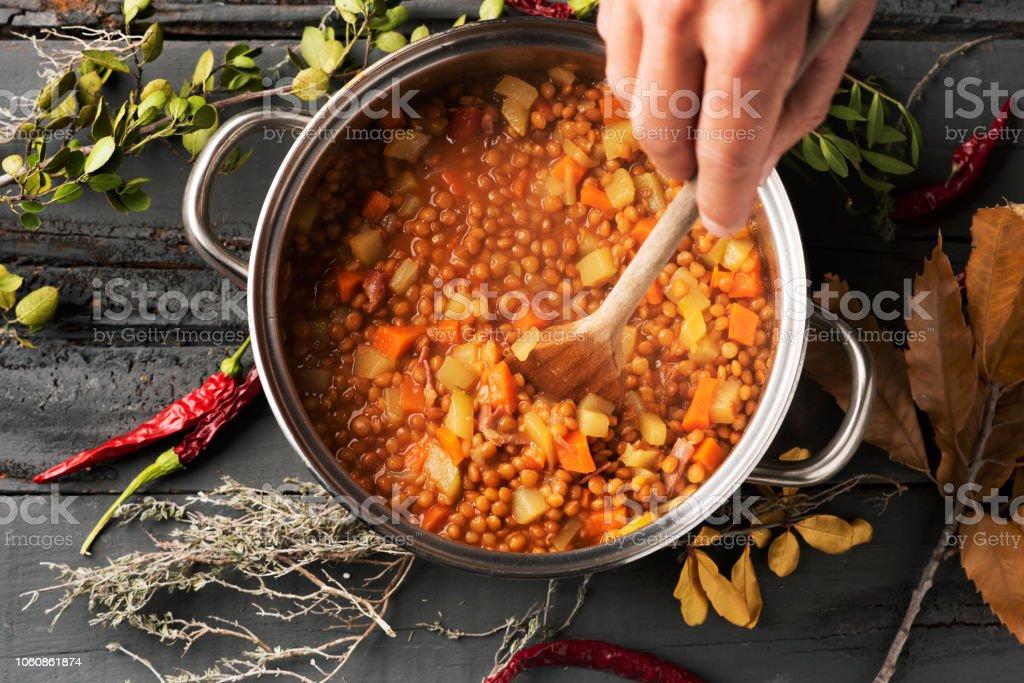 man preparing a vegetarian lentil stew stock photo