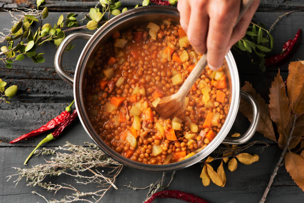 man preparing a vegetarian lentil stew high angle shot of a young caucasian man stirring a lentil stew, with a wooden spoon, in a stainless steel cooking pan placed on a gray rustic wooden table stew stock pictures, royalty-free photos & images