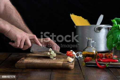 istock Man preparing an Italian pasta on a rustic wooden table 696497174