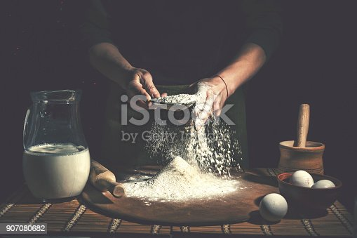 istock Man preparing bread dough on wooden table in a bakery close up. Preparation of Easter bread. 907080682