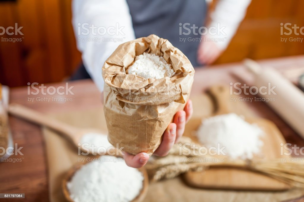 Man preparing bread dough on wooden table in a bakery close up stock photo