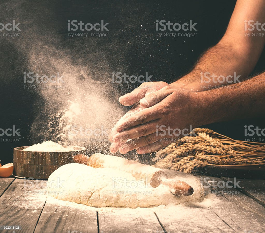 Man preparing bread dough on wooden table in a bakery stock photo