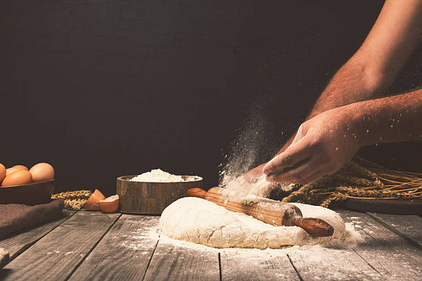 man preparing bread dough - bakeries stock photos and pictures