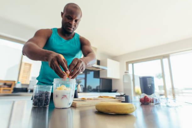 mann, die zubereitung des frühstücks in der küche - diät shakes stock-fotos und bilder