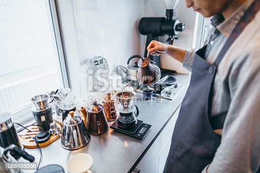 A man is preparing coffee in his kitchen.