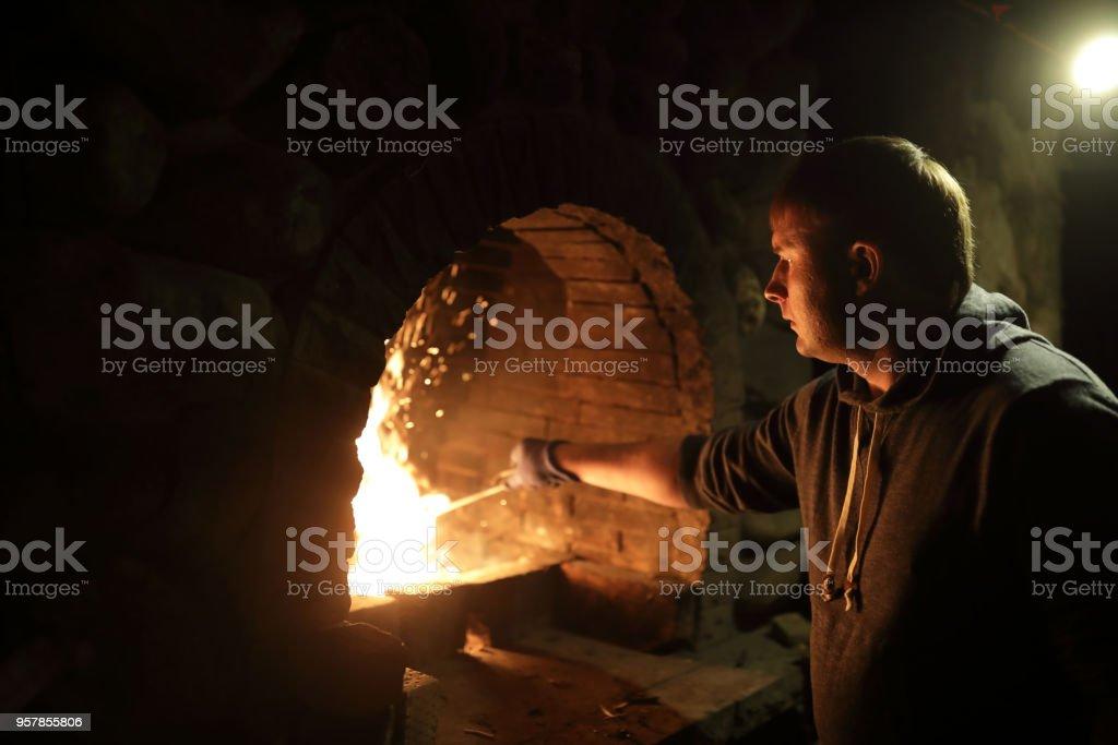Man preparing fire in stove stock photo