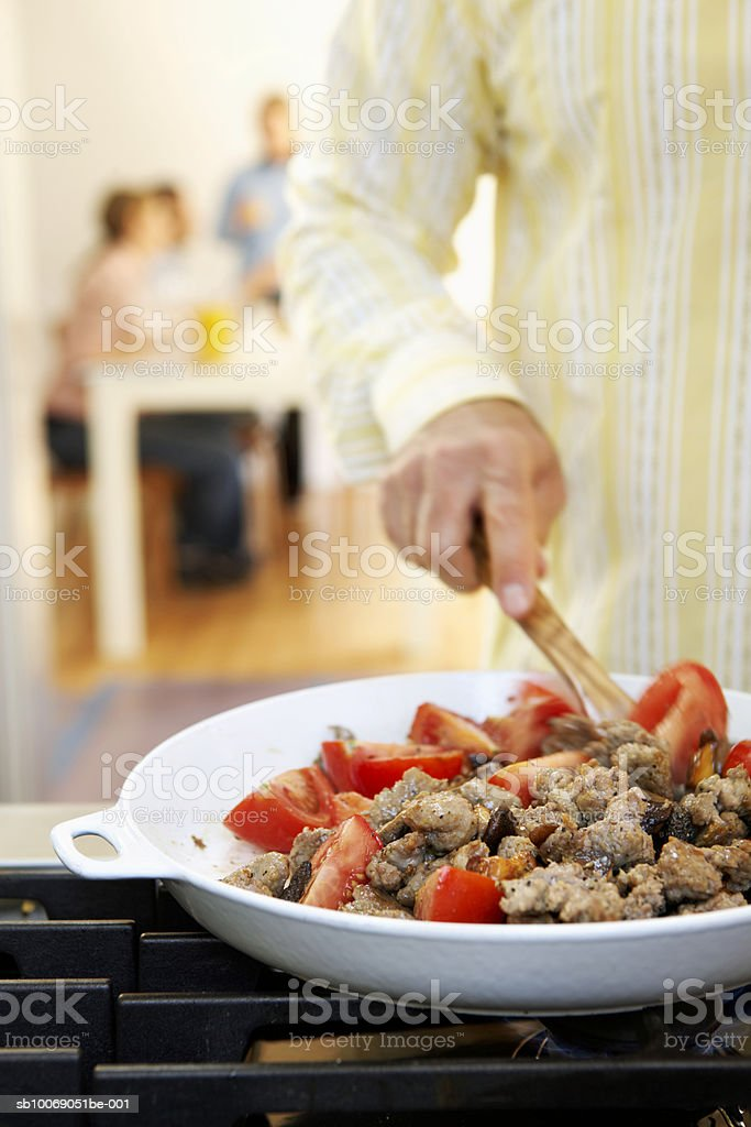 Man preparing  food on stove, people in background, mid section 免版稅 stock photo