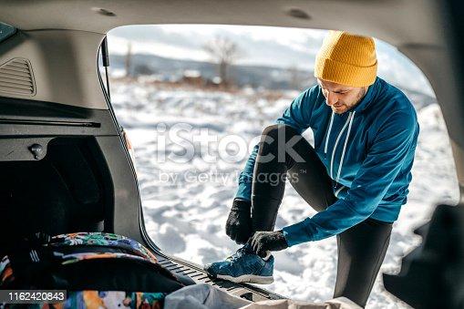 istock Man preparing for run on snow 1162420843