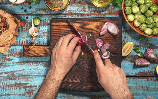 Man preparing healthy food on kitchen wooden table, top view