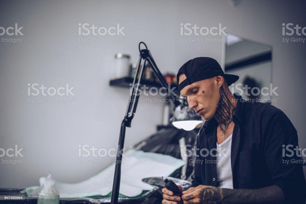 Man preparing tattoo machine for work stock photo
