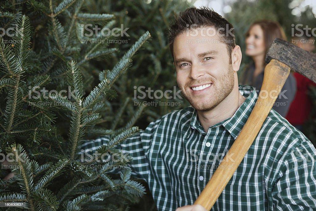 Man preparing to chop down Christmas tree at farm royalty-free stock photo