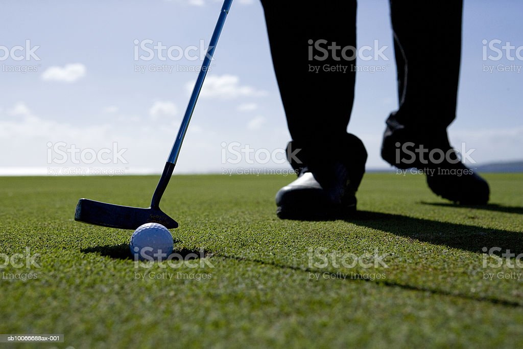 Man preparing to putt, low section (differential focus) royalty-free stock photo