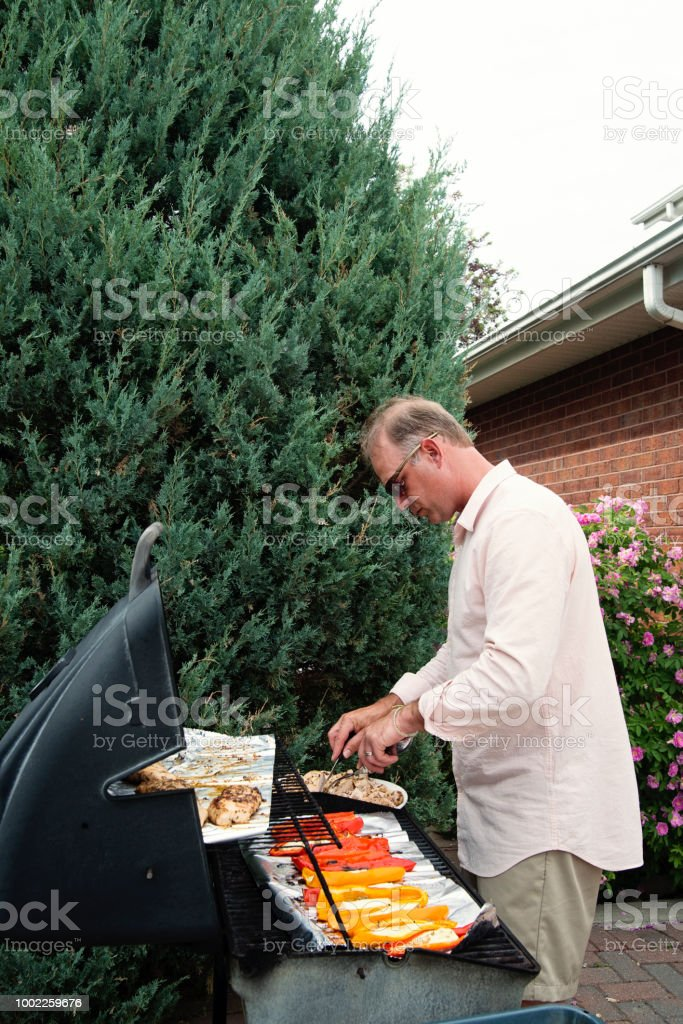 Man preparing vegetables and meat on family barbecue. stock photo