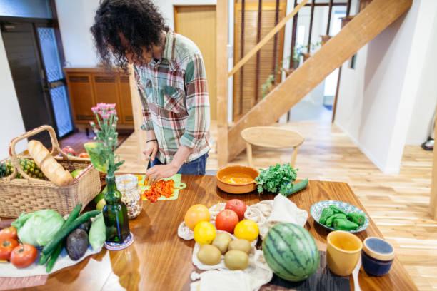 mann bereitet vegetarisches essen für home-party - jamaikanische party stock-fotos und bilder