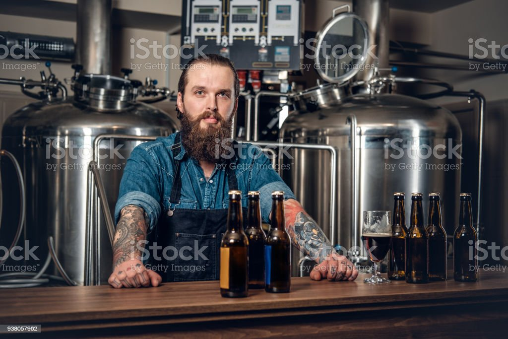 A man presenting beer in the microbrewery. stock photo