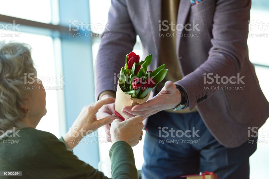 Close-up of loving man giving beautiful bouquet of burgundy tulips to...