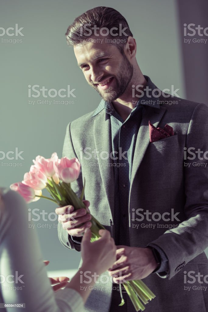 Man presenting flowers to woman foto stock royalty-free