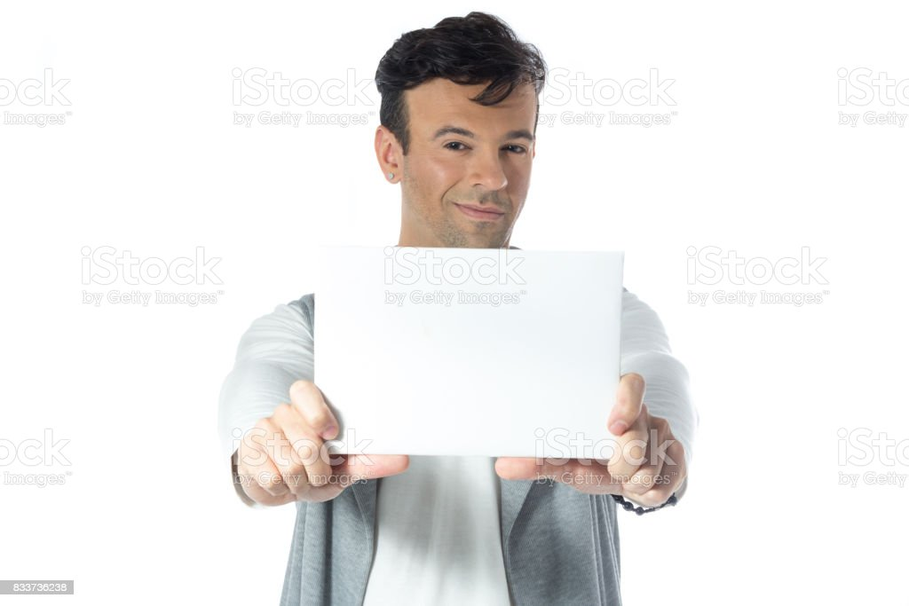Man presents space for advertising content. Handsome brazilian wearing gray and white clothes, neutral. stock photo