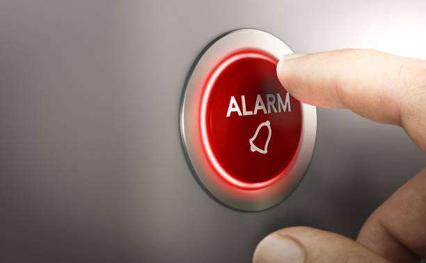 Man pressing a red security alarm button. stock photo