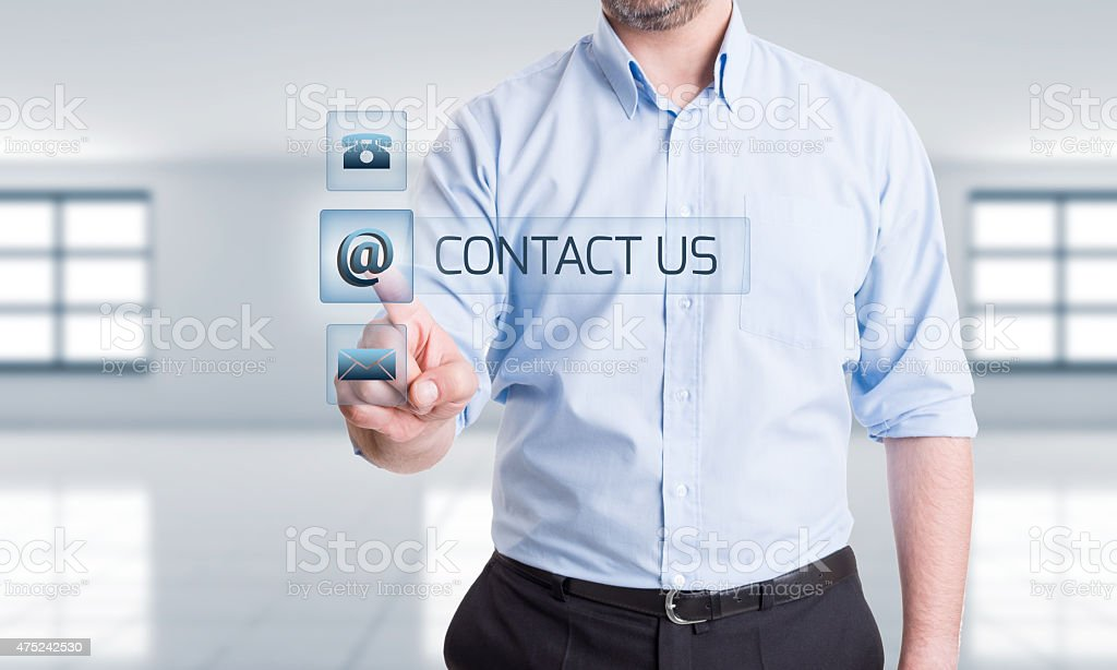 Man pressing contact us button on transparent touch screen stock photo