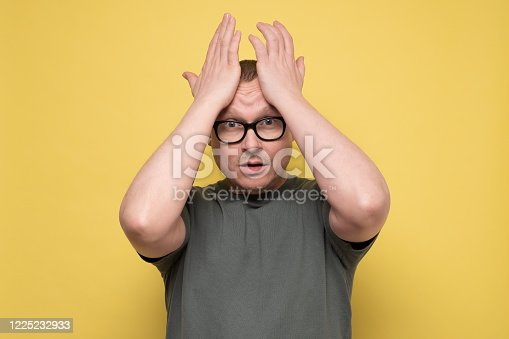 Troubled worried and nervous concerned man pressing hands to head panicking being in perplexed situation, forgetting important thing. Studio shot on yellow wall.