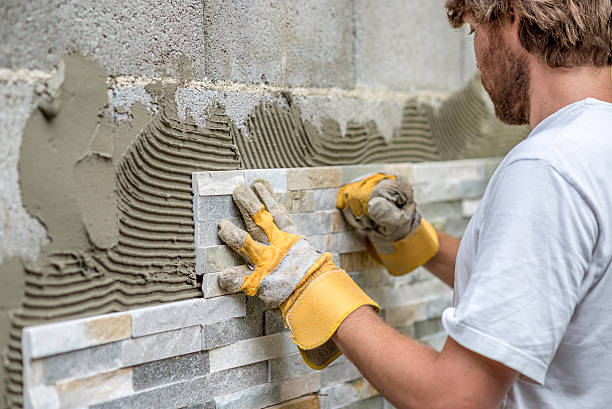 Man pressing ornamental tile into a glue on a wall stock photo