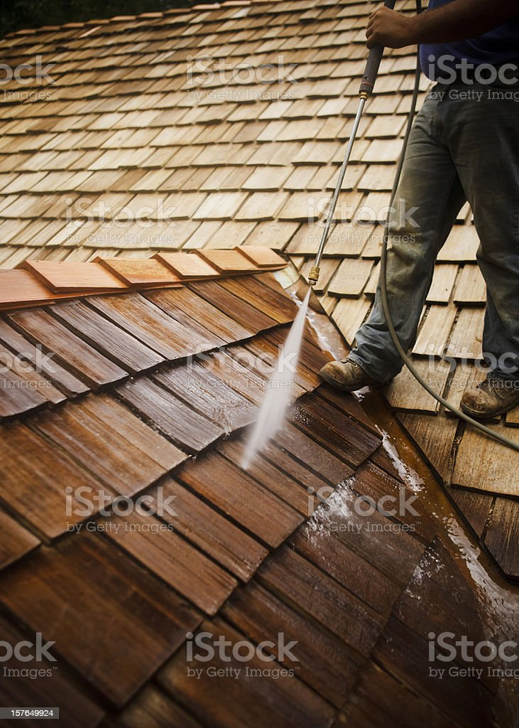 Man Pressure Washing a Roof stock photo