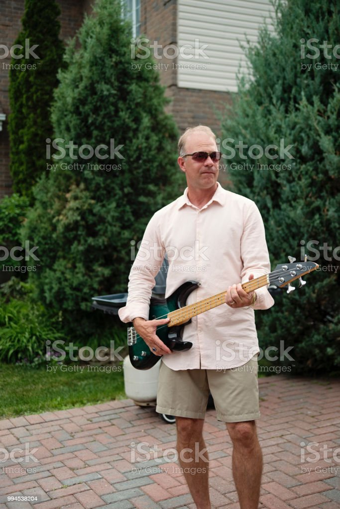 Man pretending to be a rock star in family driveway. stock photo