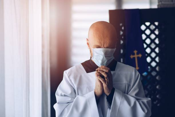 Man priest in medical mask praying with cross and rosary. stock photo