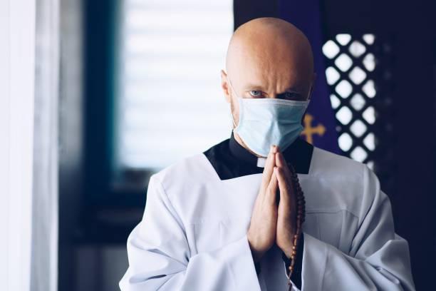 Mann Priester in medizinischer Maske beten mit Kreuz und Rosenkranz. – Foto