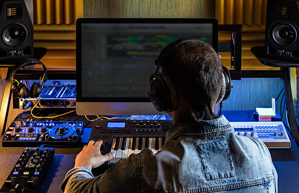 Man produce electronic music in studio stock photo
