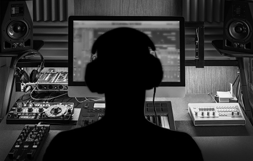 Man produce electronic music in project home studio. Black and white monochrome image