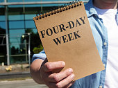 istock Man proposes four-day week sign. Notepad in hand. 1263863851