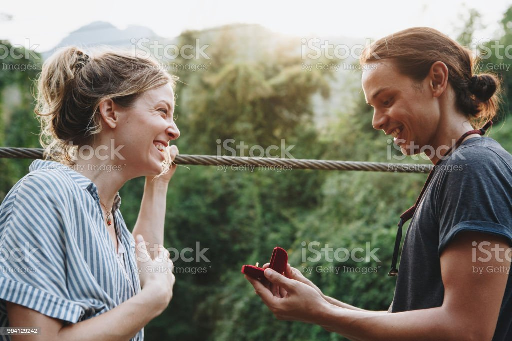Man proposing to his happy girlfriend outdoors love and marriage concept stock photo