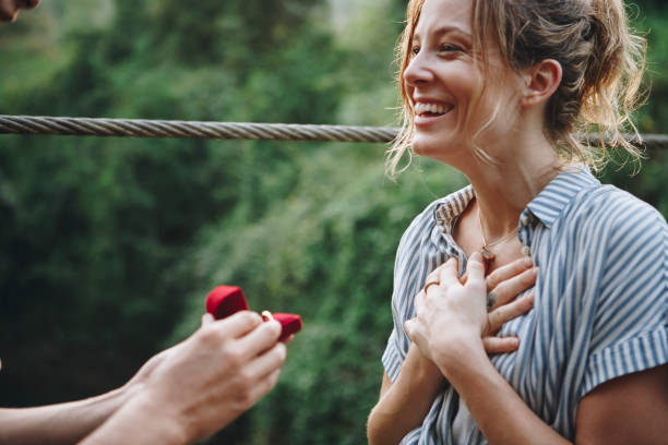 Man proposing to his woman with a red box stock photo