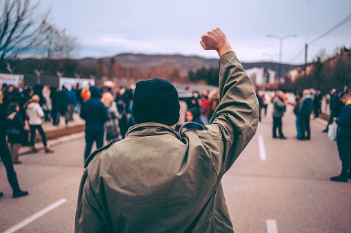 Man protests in the street with raised fist