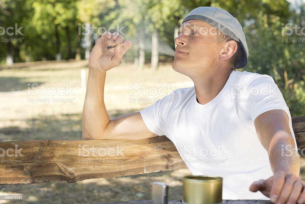 Man puffing on a cannabis or marijuana cigarette royalty-free stock photo
