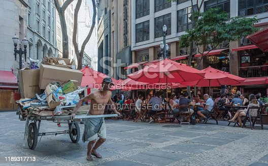 Sao Paulo city, Sao Paulo state, Brazil - October 05, 2019:Man pulling a recyclable trash wagon in front of a fancy restaurant in Sao Paulo.