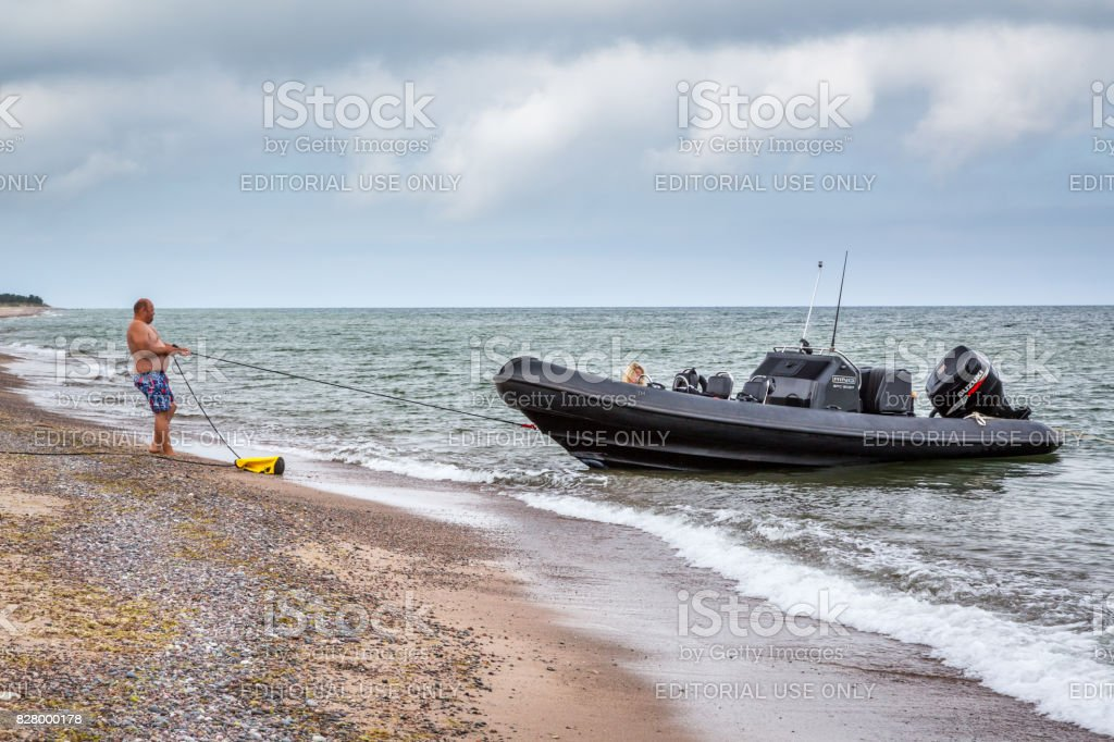 Man pulling a rope to a speedboat. royalty-free stock photo