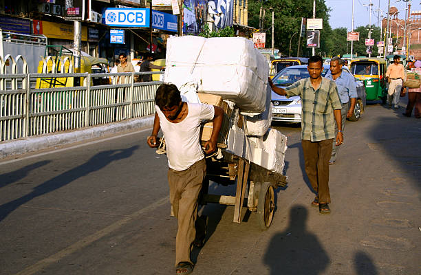 man pulling cart laden with goods, delhi, india stock photo