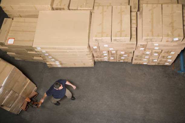 Man pulling dolly skid with boxes in distribution warehouse stock photo