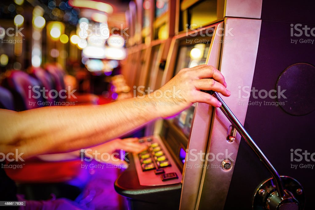 Man pulling down lever of slot machine in casino stock photo