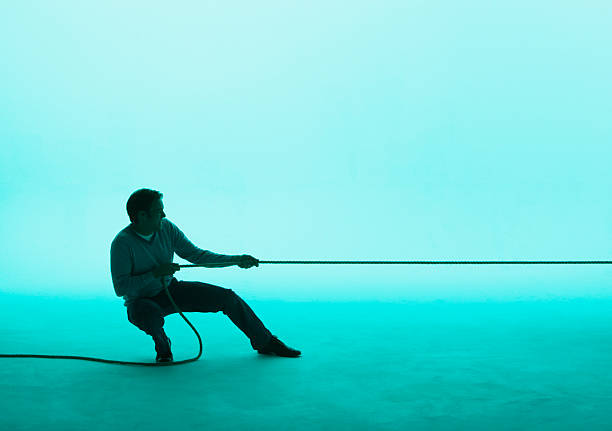 Man pulling on a rope  pulling stock pictures, royalty-free photos & images