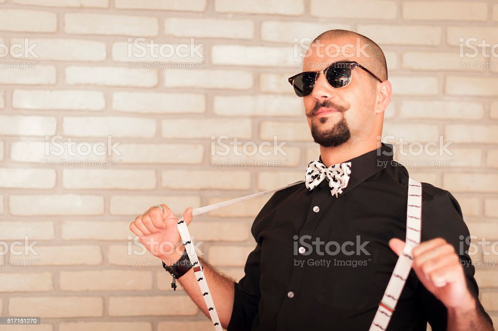 Man pulling on his suspenders with a cocky smile stock photo
