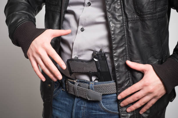 Man pulling out a gun ready to shoot stock photo